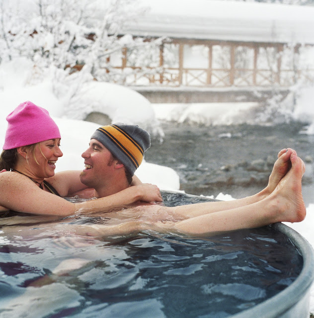 Young, happy couple laughing romantically while sitting the hot tub outside in the winter.