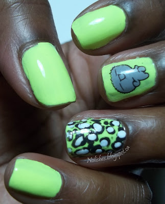 Nail stamping manicure featuring a pastel neon yellow base manicure embellished with a dark grey and white leopard print on the ring finger, and a cute grey cartoon monster on the middle finger.