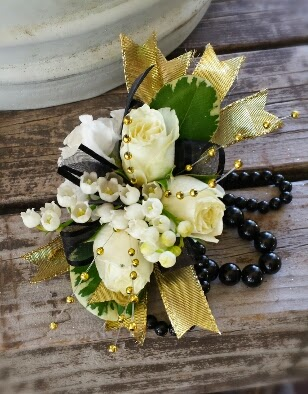 Wrist corsage design in gold & black featuring white roses and  $$$$ Lily of the Valley accents.