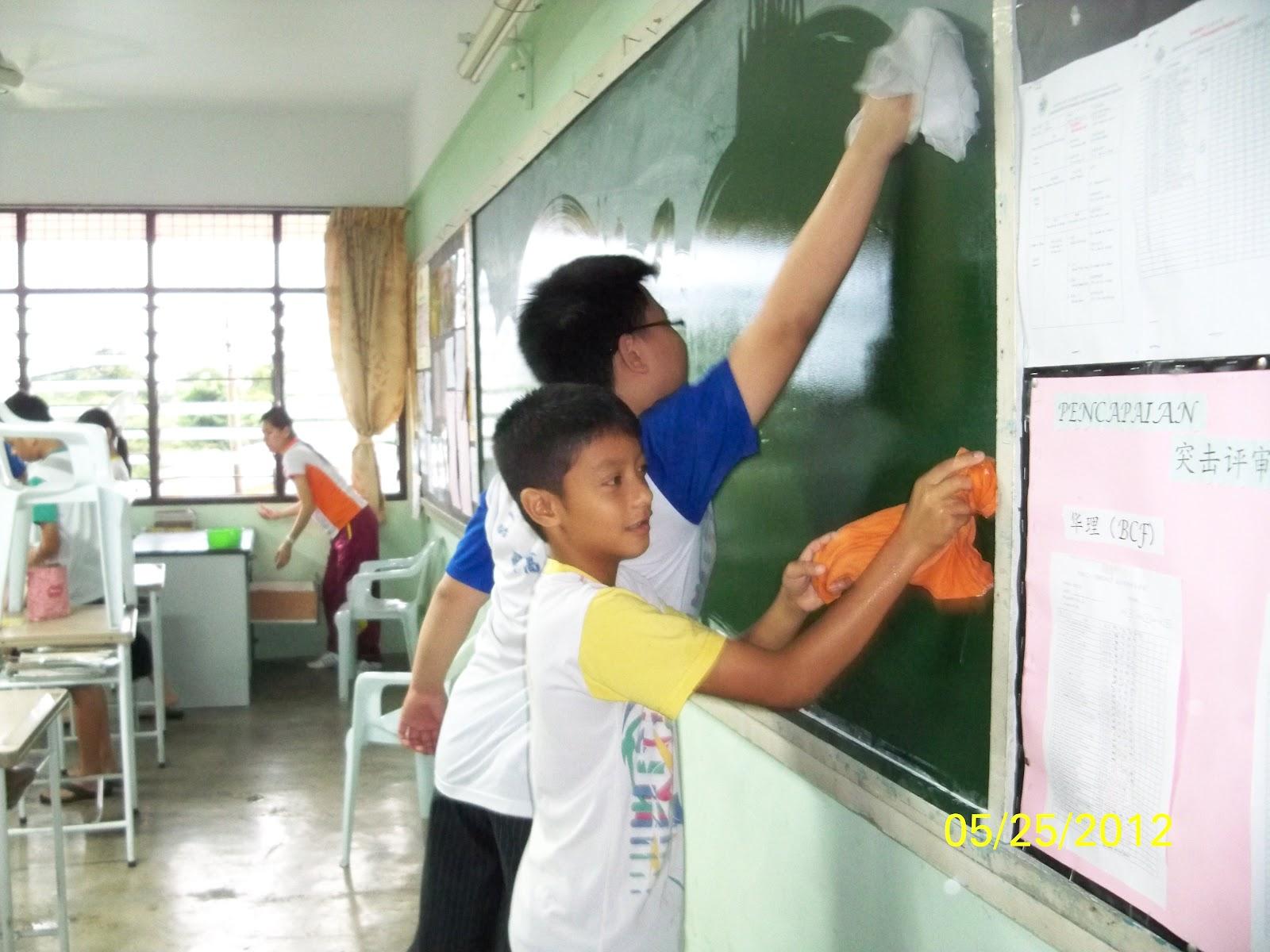 Murid-murid membersihkan bilik kelas.