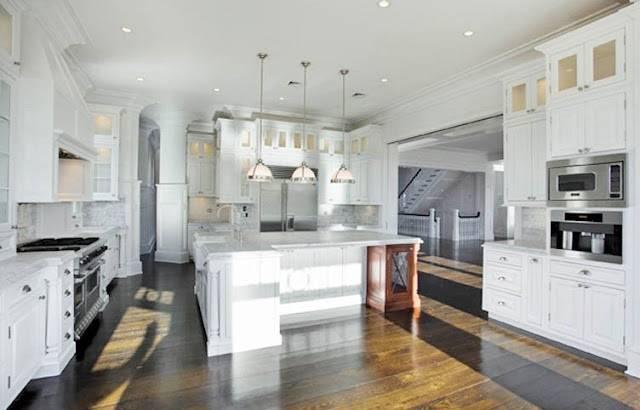 kitchen with hardwood floors, white marble counters, stainless steel appliances, white cabinets and a huge island with pendant lights
