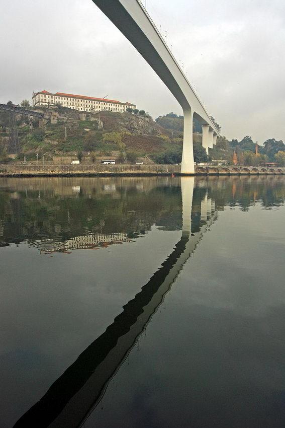 Foto da ponte de topo com a sua imagem reflectida nas águas do rio Douro
