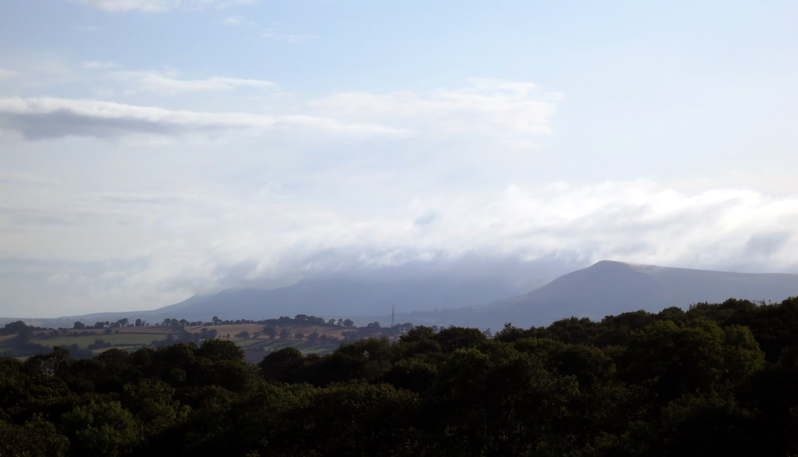 Clouds gather over distant hills.