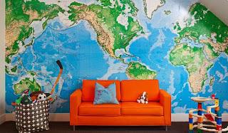 sala com sofá laranja e um grande mapa mundi na parede.