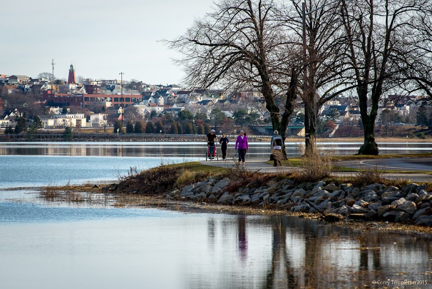 Portland, Maine USA December 2015. Folks making their way around the Back Cove Trail on Christmas morning. Part of Munjoy Hill and the Portland Observatory are in the background.