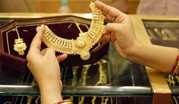 A woman shops for a golden necklace