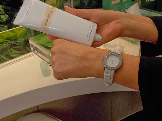 A picture of creme de la mer body refiner next to a hand that has been exfoliated with it
