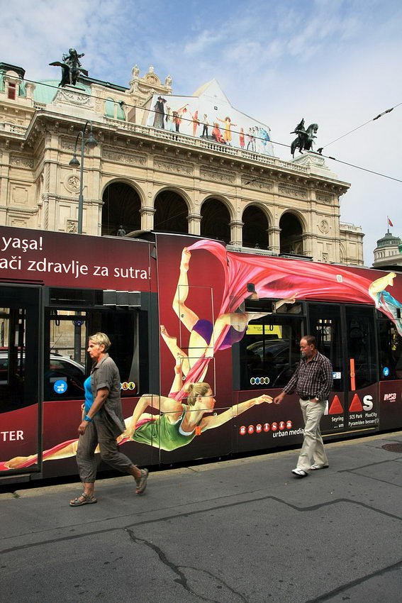 Foto em frente à Ópera de Viena, com o Metro parado e duas pessoa a passarem. Ao fundo a parte superior do edifício