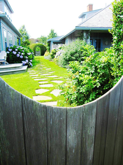 View of a stone walkway in a backyard in Nantucket from over a wooden fence