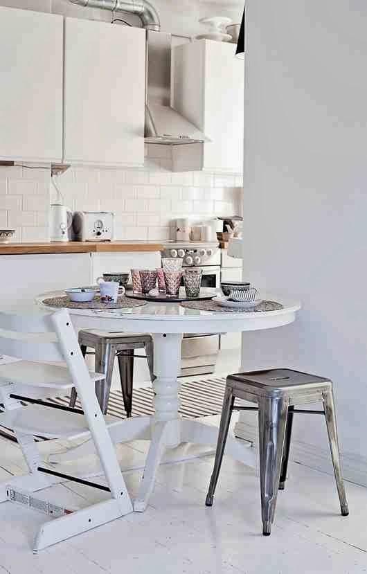 Biała kuchnia, biała podłoga, metalowe srebrne taborety, biały stół drewniany, białe krzesło dla dziecka