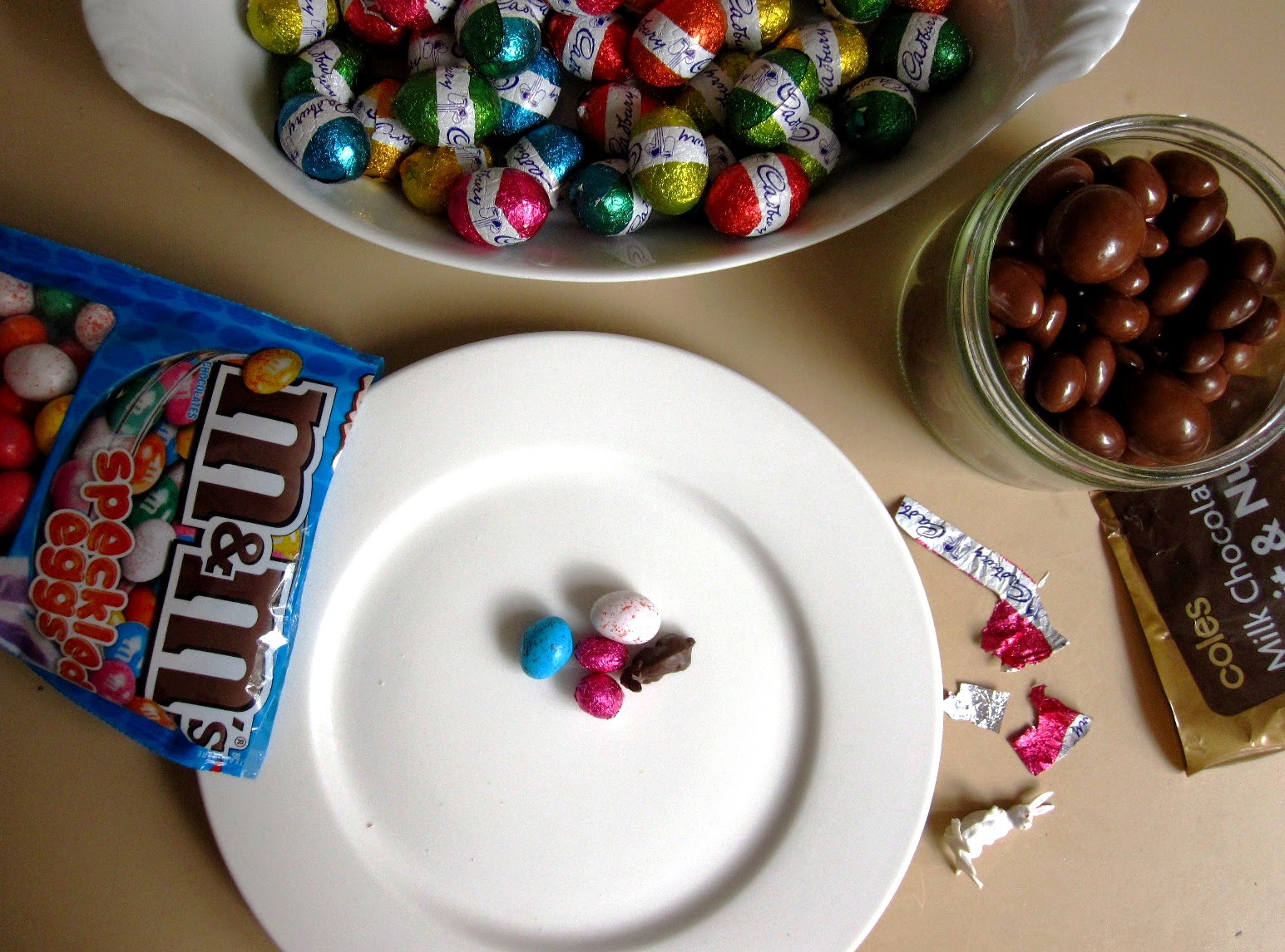 A bag of M&M speckled eggs, a bowl of Cadbury mini eggs and a jar of milk chocolate fruit and nut mix arranged around a plate with dolls' house-sized Easter eggs on it.