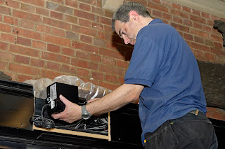 Man on ladder installing LED projector box