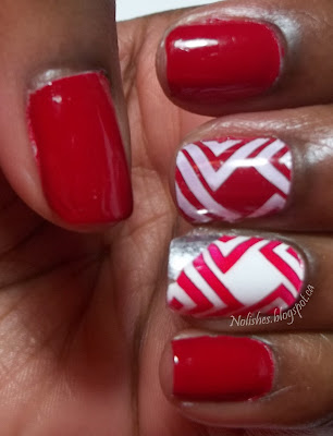 Red and white nail stamping manicure with nails stamped geometric print on ring and middle fingers. The ring finger accent nail is white stamped with red, with a diagonal stripe of silver on one corner.