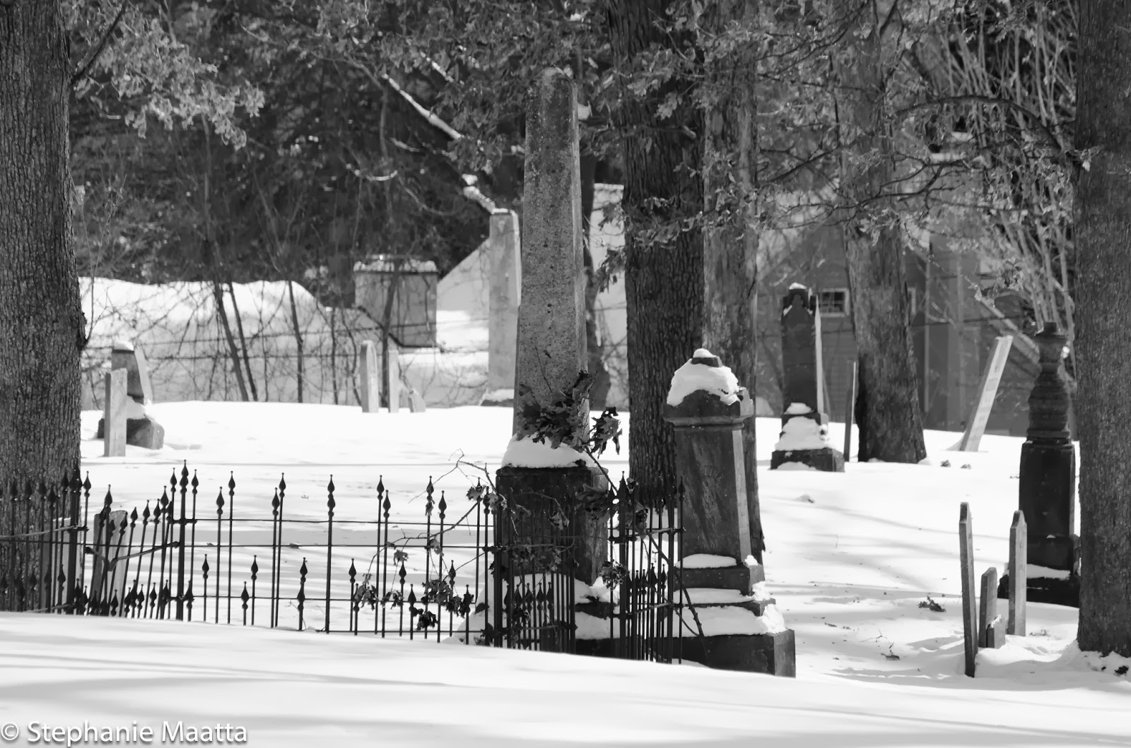 grave stones covered in snow in black and white