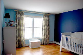 Baby's room with crib and large window with drapes