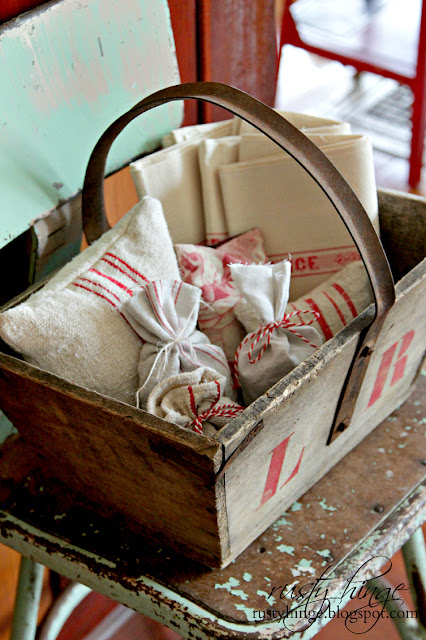 Vintage French trug filled with red and white antique French linens