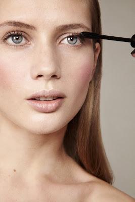 photographe beauté paris, model applying mascara, clean skin, long eyelashes
