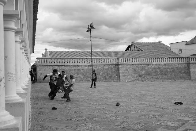 NIños jugando al fútbol en una plaza