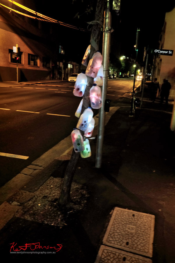 Illuminated plastic milk containers on a light pole - Abercrombie Street Chippendale - Photo by Kent Johnson.