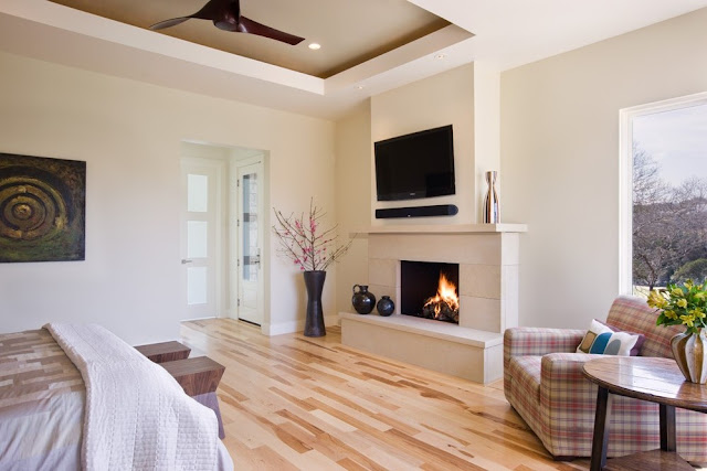 Photo of large bedroom with big fireplace and tv above it