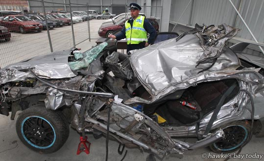 Senior constable Andy Clinton, pictured with a Mitsubishi Lancer Evolution IV commonly known as an Evo 4, a car in which a person died in a fatal accident on Farndon Rd, Hastings, last week. Pictured at Hawke's Bay Towing, Whakatu, Hastings.