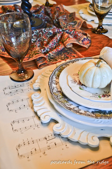 Vintage sheet music for placemats, baby pumpkins, vintage dishes and more in this cozy breakfast room tour from Postcards from the Ridge.