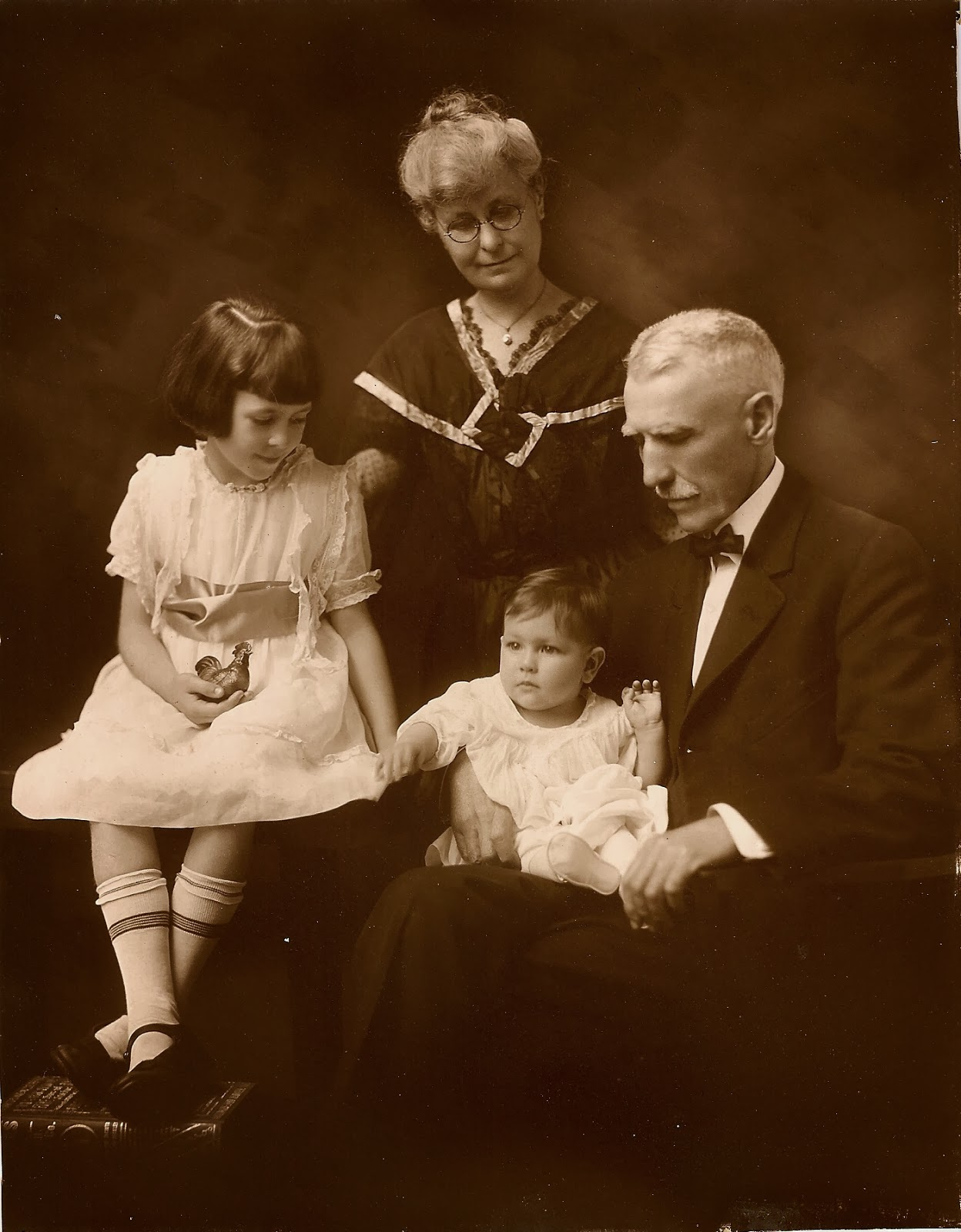 A studio photo of an old couple and two grandchildren.