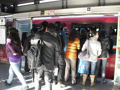 Passengers getting ready to board a pretty crowded Transmilenio