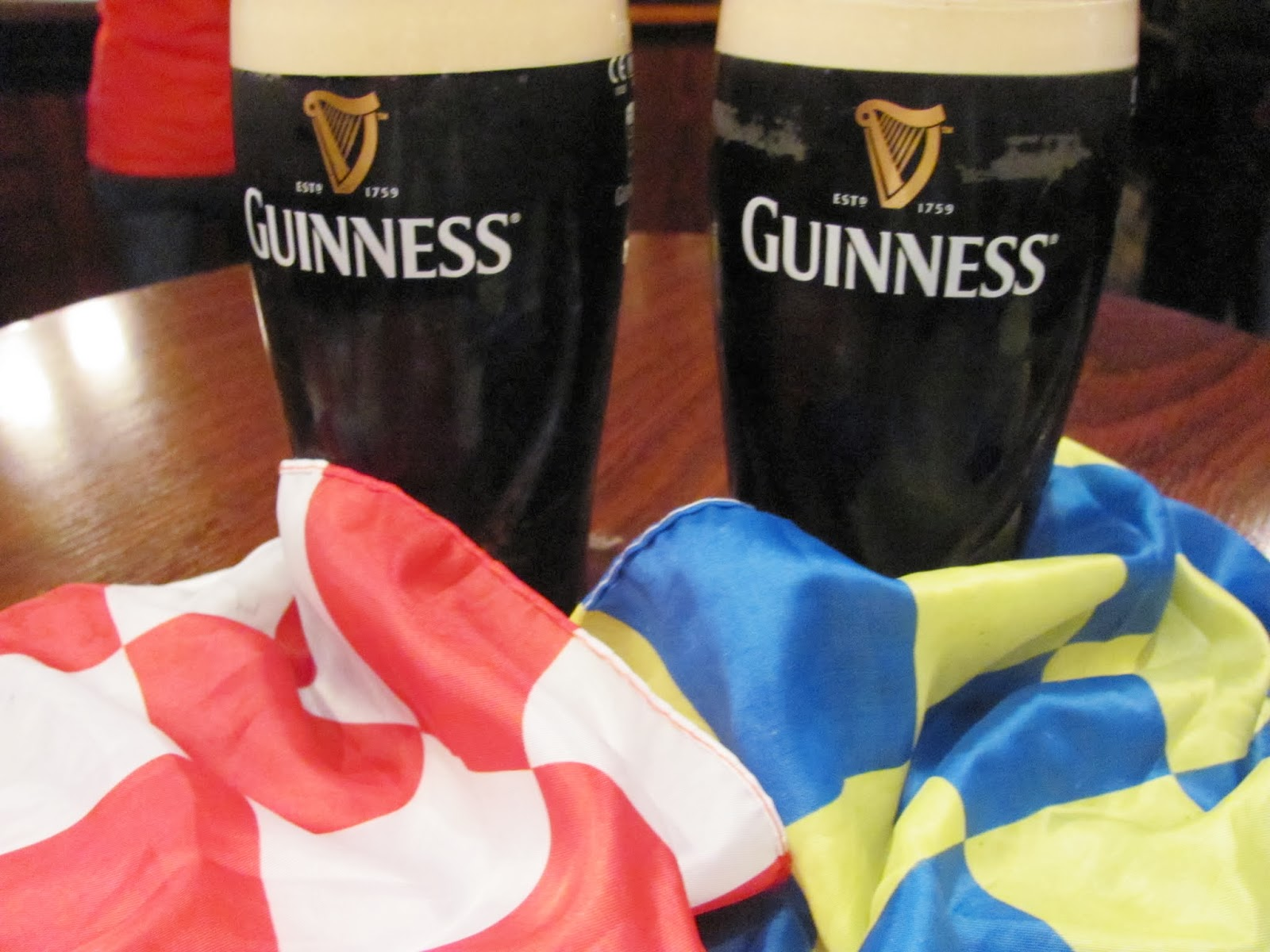 Two flags, red and white for Cork and blue and gold for Clare, sit with two pints of Guinness during the first All-Ireland Hurling Final 2013 in Dublin, Ireland