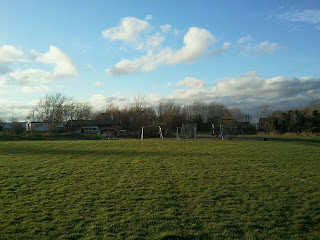 Field with playpark in the distance