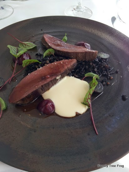 a black plate with an arrangement of seared emu loin, spiced black pudding, smoked potato and Illawarra plums