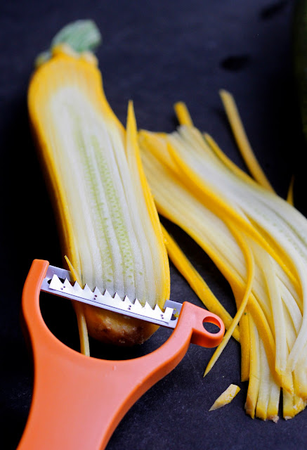 summer squash being cut with a vegetable peeler to make Zucchini Noodles with Chicken and Tangy Peanut Sauce