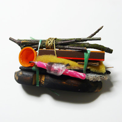 This brooch consists of small burnable items, including a birthday cake candle, bound together with string and stacked on top of each other, conjuring the idea that they are ready for burning.