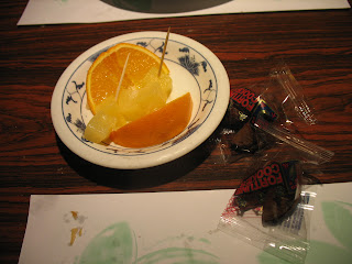 A dish of oranges, pineapple, and fortune cookies