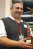 Garett Holm holding a bottle of Maker's Mark bourbon, with a braille label