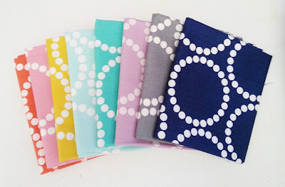 folded fabrics arranged in color order featuring a dotted circle pattern