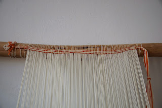 The starting border bound to the top bar of the loom with the warp threads suspended