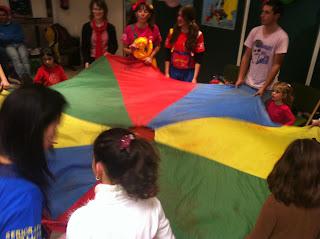 En la imagen se observan a los niños sujentando una gran lona de colorines con un agujero en el centro por donde se debe colar una pelota.