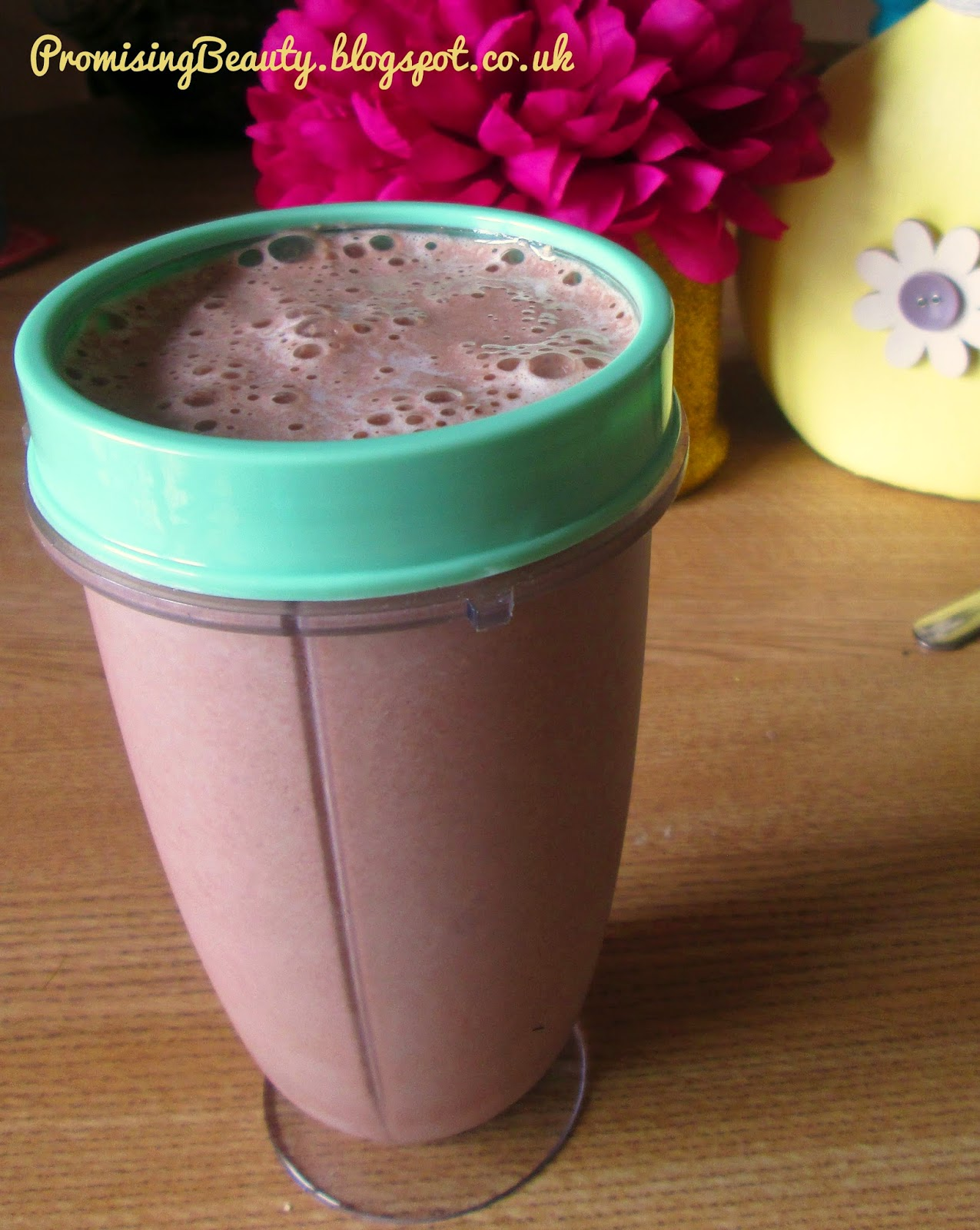 Healthy breakfast milkshake smoothie. Filling, cheap and clean. Energy ingredients made in a bullet blender. Chocolate and banana. Purple flower and pinterest crafts in the background.