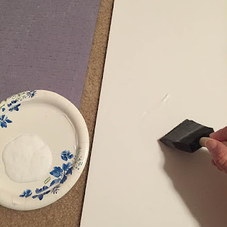 Foam brush applying glue to a white foam core board