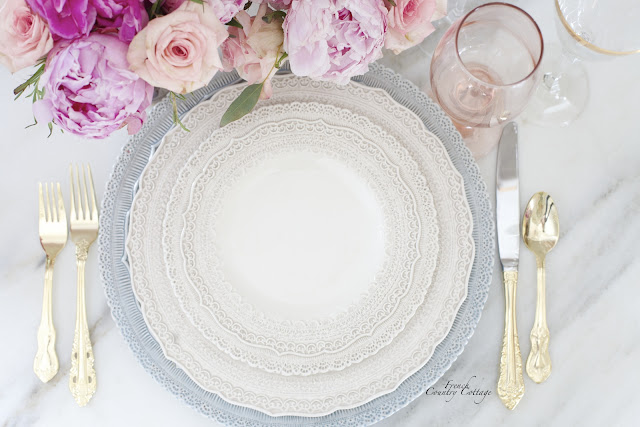 Lace dishes with gold flatware and flowers