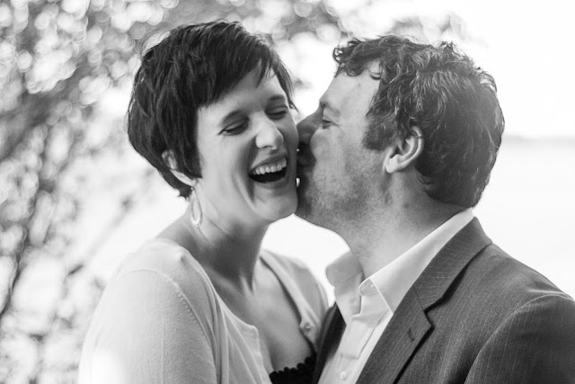 husband kissing wife on cheek while she laughs