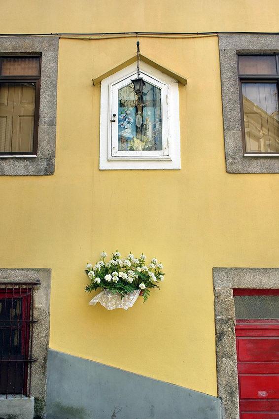 Alminha embutida numa parede de casa de habitação e cesto de flores logo abaixo decorado com tecido rendado também branco