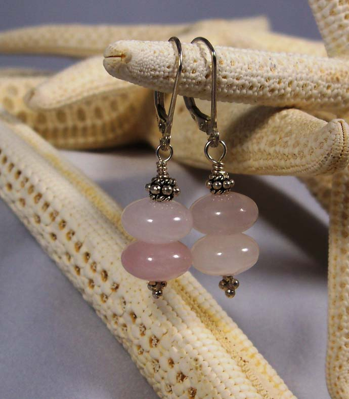 A pink handmade pair of earrings created by Cynthia from Antiquity Travelers