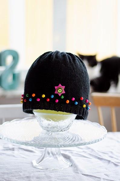 svart stickad mössa med pärlor i glada färger