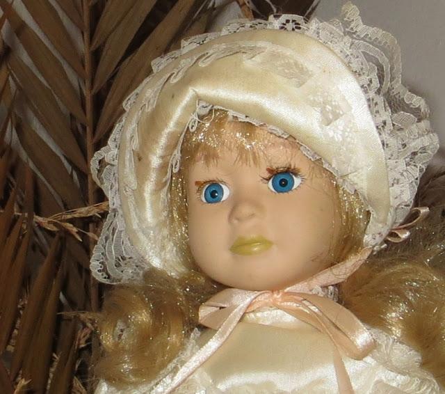 Fotografia macro com ampliação da face de Boneca Antiga de Porcelana para criança em cima de guarda fato