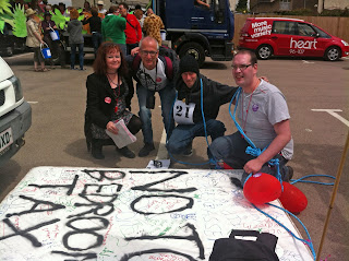 Four people crouch around a mattress with writing on it 'No To Bedroom Tax' is writted in big letters