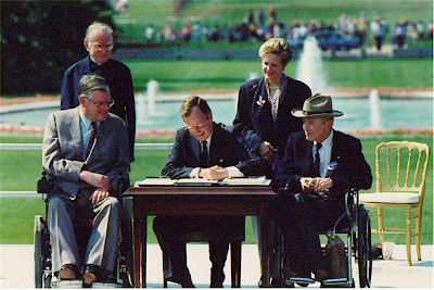 President Bush is seated at a table outside, signing a document. Reverend Harold Wilke and Sandra Parrino stand behind him, Evan Kemp and Justin Dart are to the left and right of him
