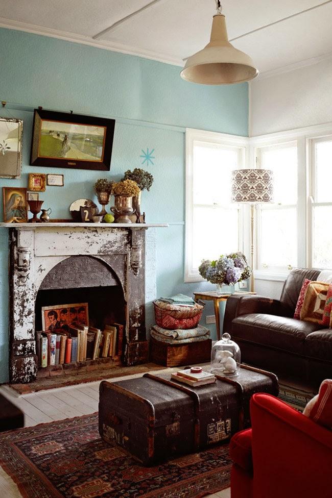 Rustykalny kominek, industrialne dodatki,  niebieska ściana w salonie, artystyczny design