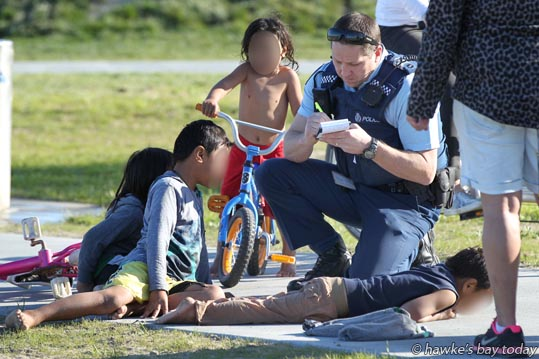 Police Sergeant Craig Ellison speaks to four children who were found swimming unattended in the sea, near the Napier Pump Track on Marine Parade, Napier. photograph